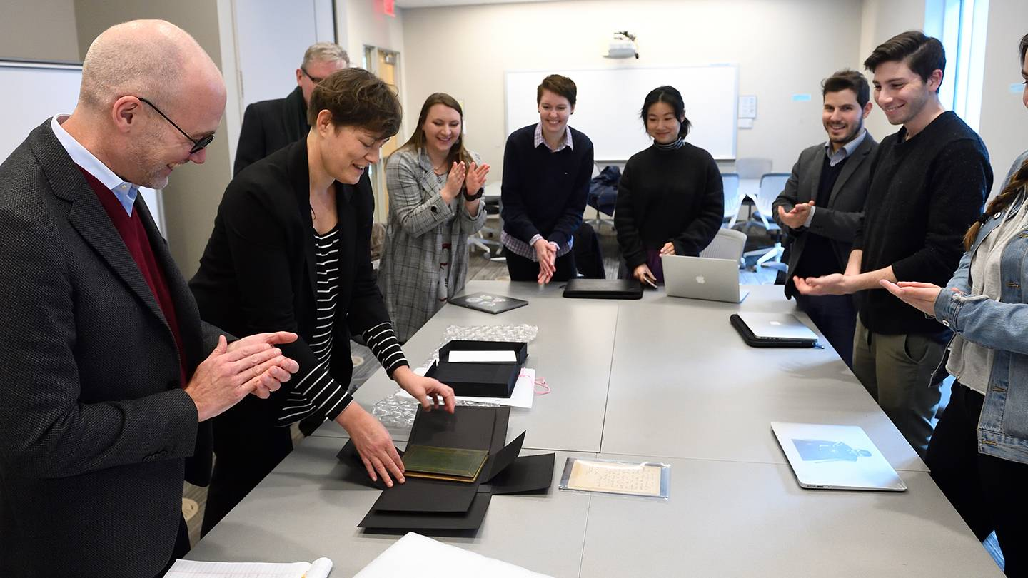 A class applauds as a book is removed from its packaging