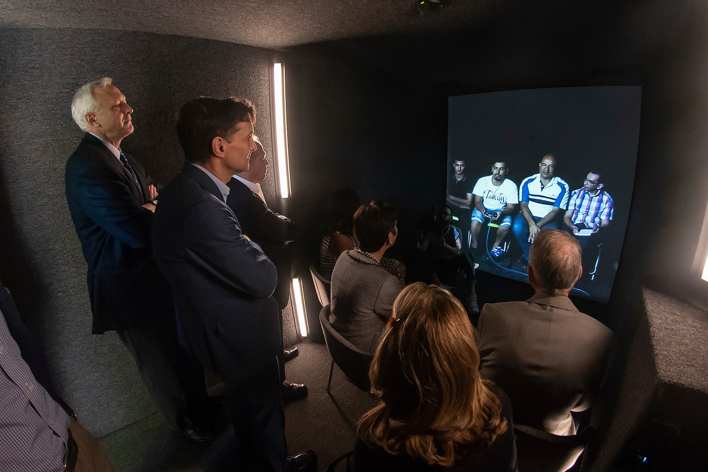 President Daniels and trustees stand in front of a screen