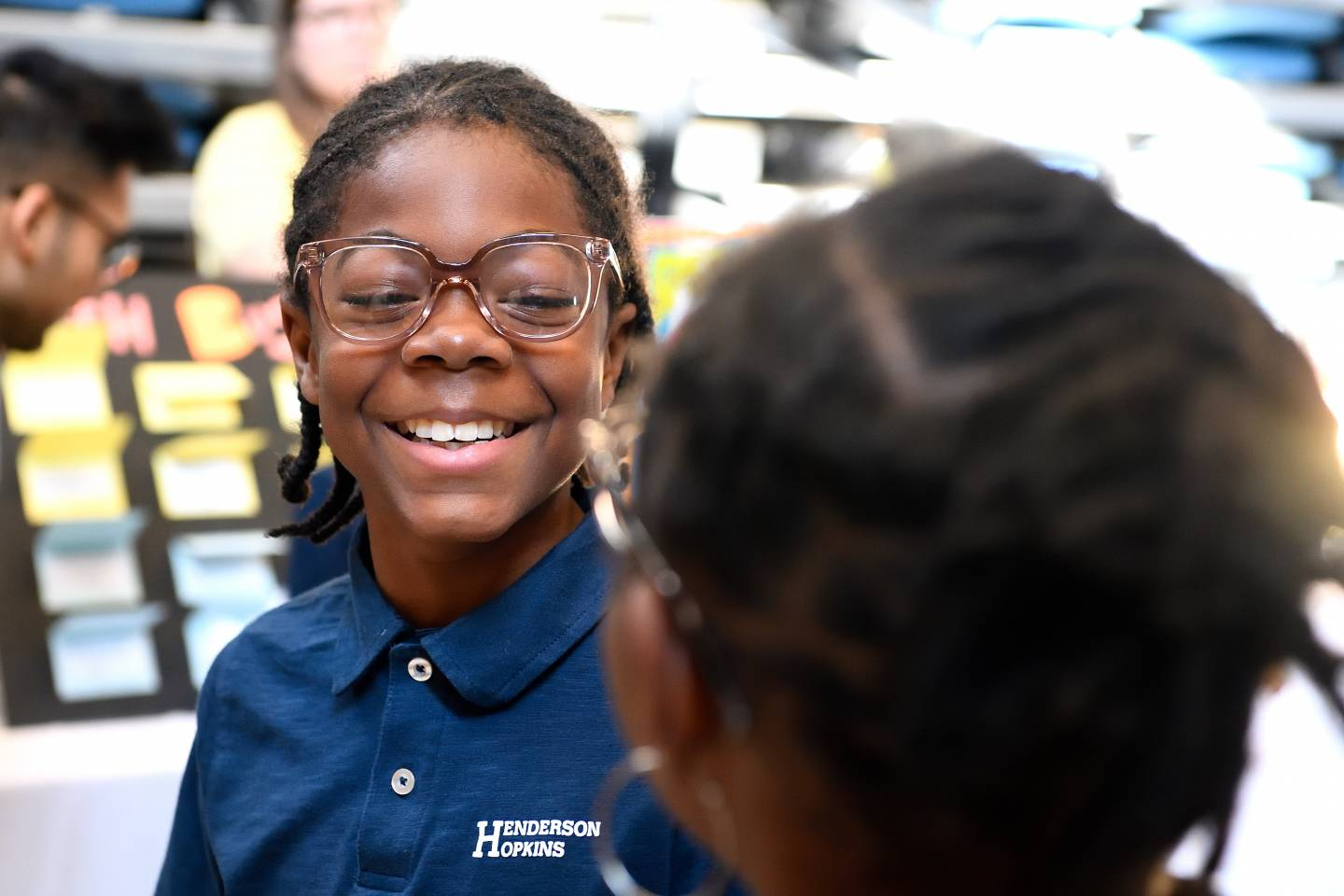 An elementary school student smiles while trying on eyeglasses