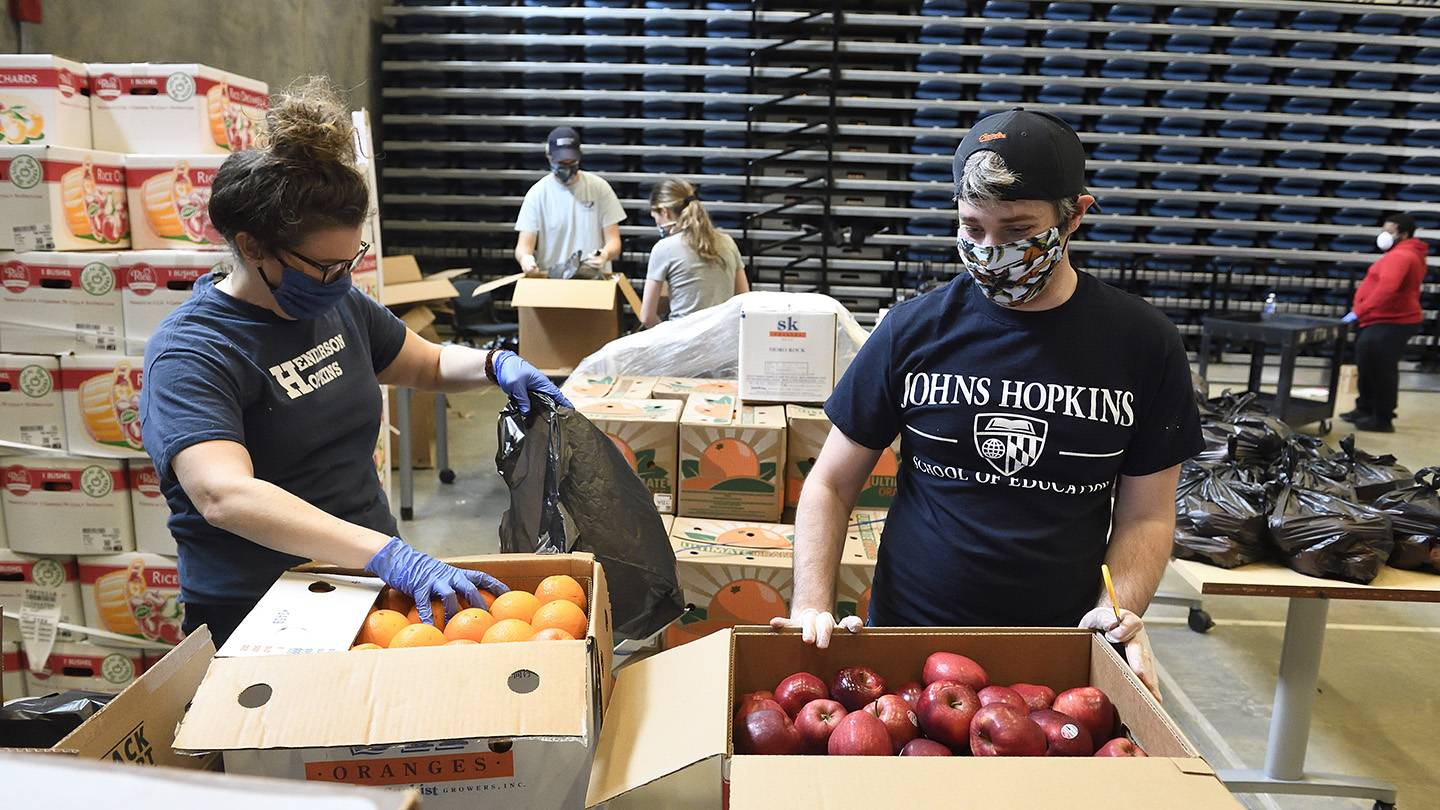 Volunteers pack food into boxes for families of Henderson-Hopkins students