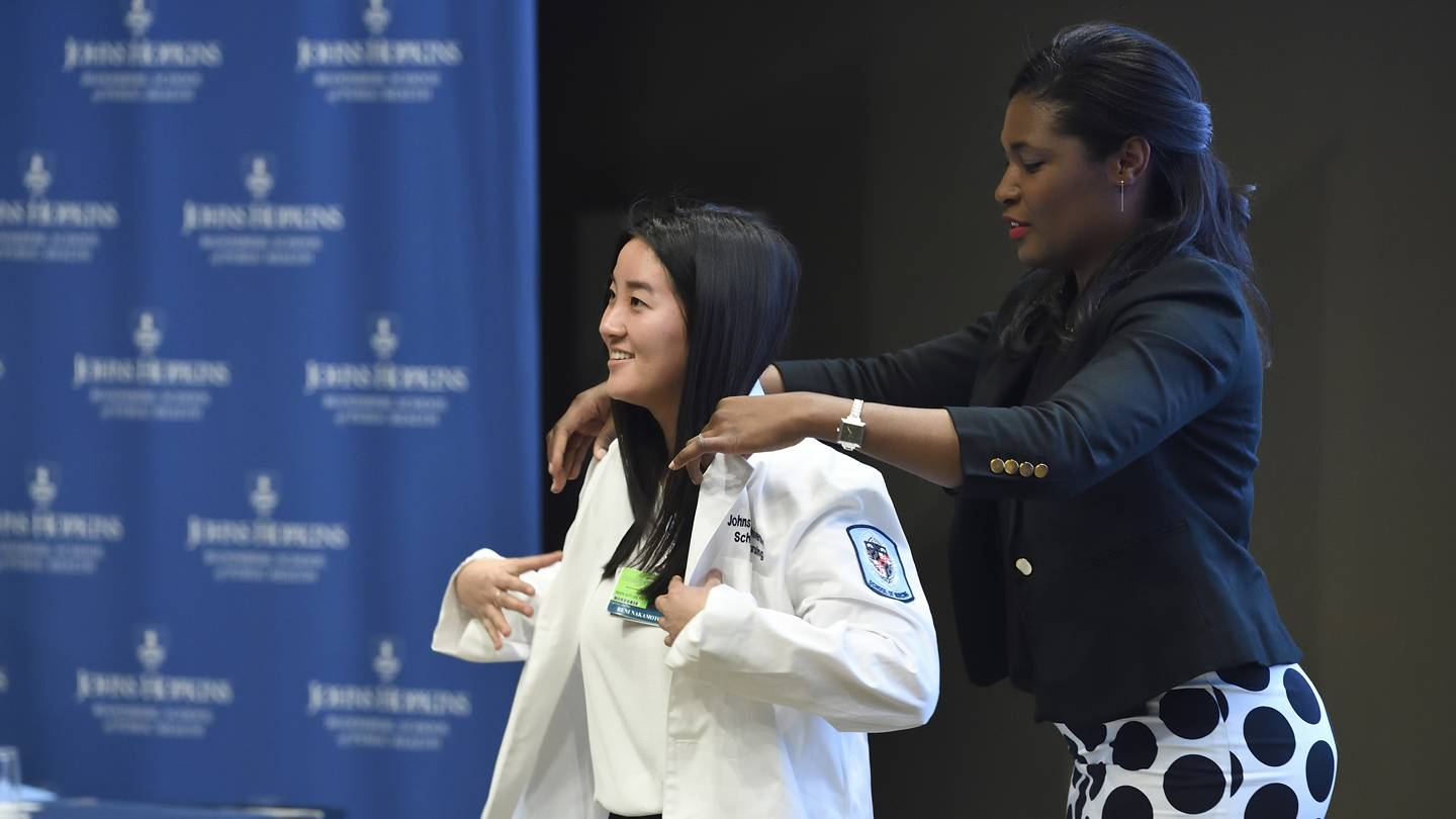 A student puts on a white coat
