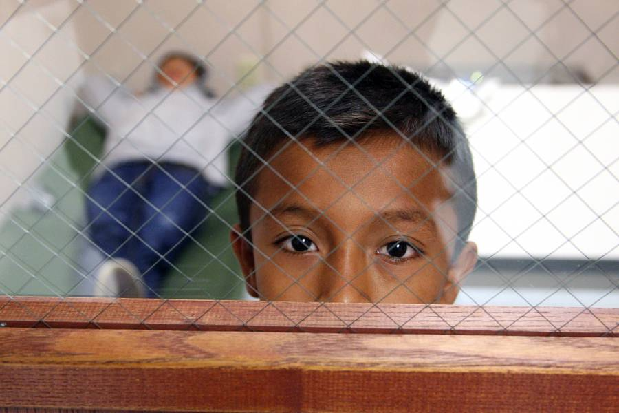A child looks out the door window from the room he is staying in at the Brownsville, Texas port of entry