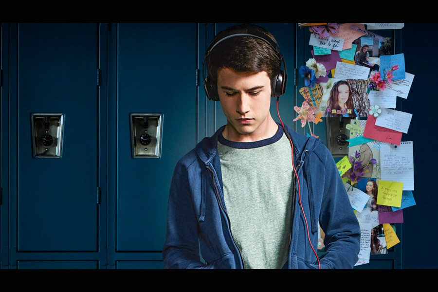 A young man wears headphones and stands in front of a line of lockers, one of which is decorated with messages and cards in a memorial