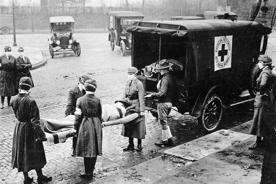 Nurses load a dead body into a Red Cross wagon during 1918 Spanish flu outbreak