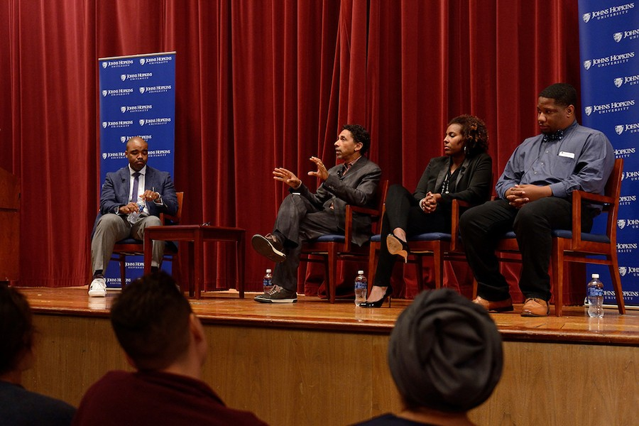 The JHU Forums on Race in America speakers sit onstage with a moderator. Robin Kelley speaks.
