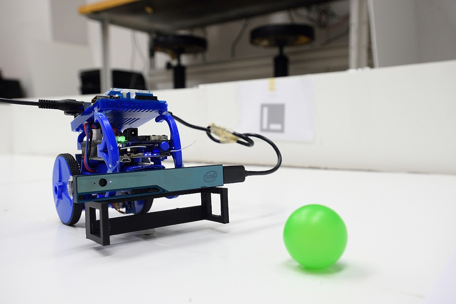 A robot pauses in front of a bright green plastic ball