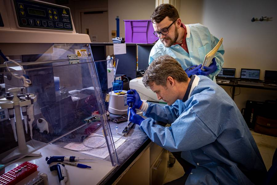 Peter Thielen and Tom Mehoke prepare a hand-held DNA sequencer for operation at the molecular diagnostics laboratory at Johns Hopkins Hospital