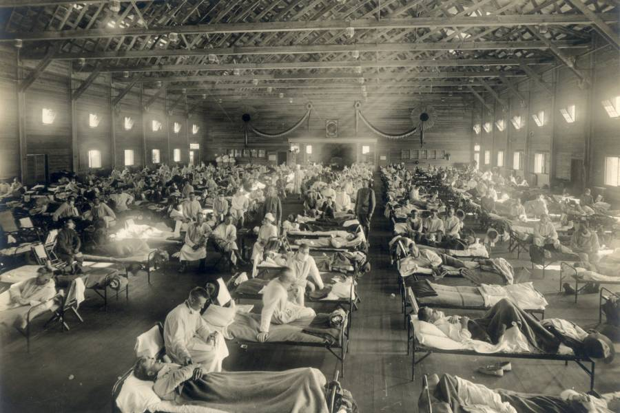 Doctors and nurses tend to the sick in an aged photograph