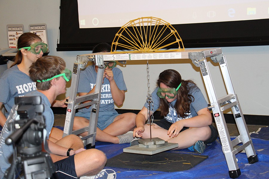 A three-person team tests their bridge with one student gently placing a weight