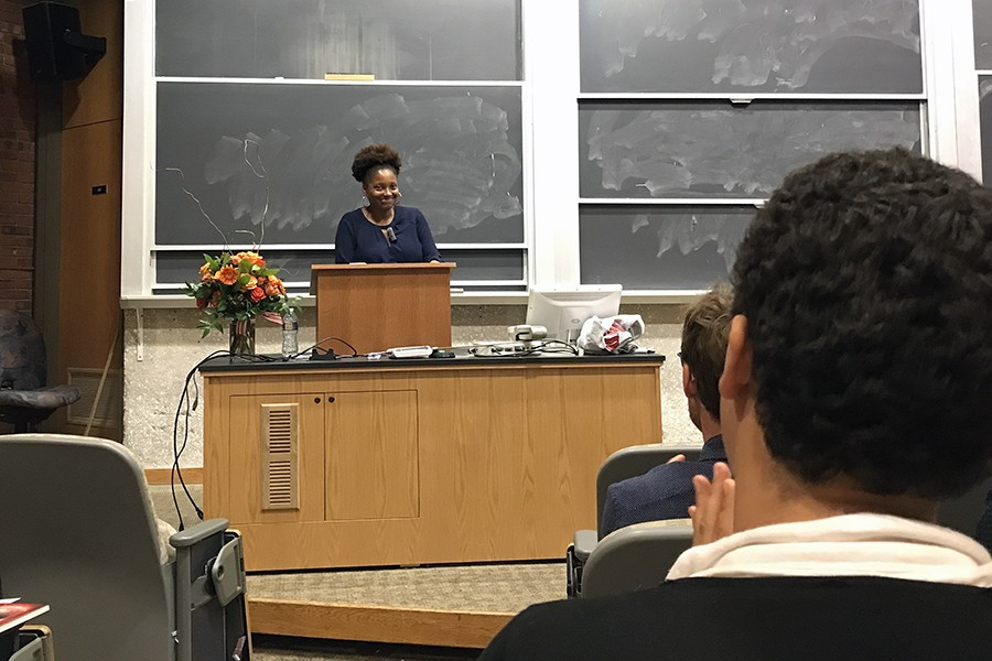 Tracy K. Smith stands at a podium and smiles while the audience applauds her