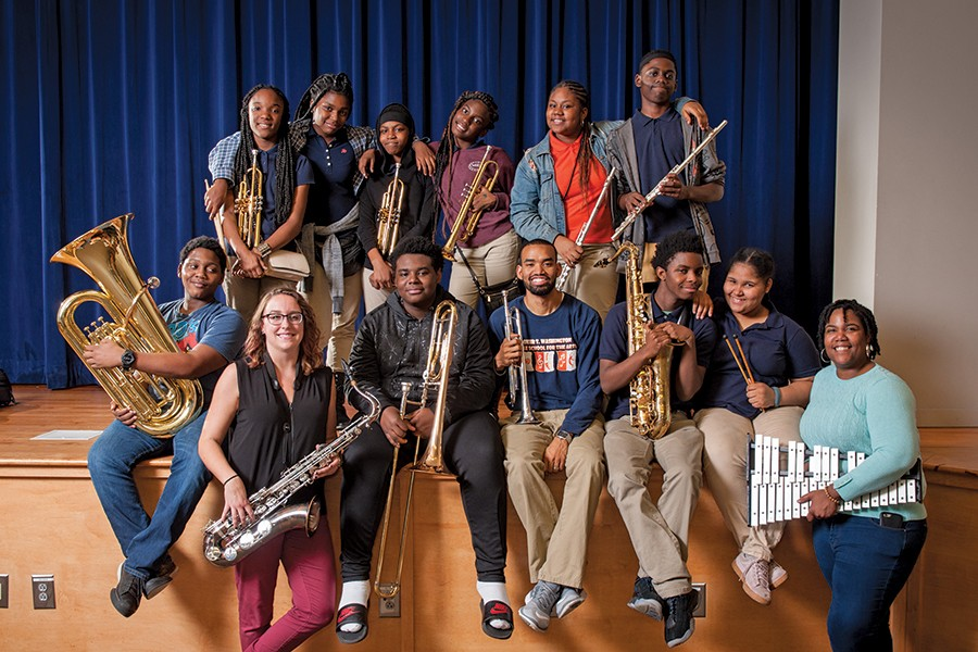 A group of people and students pose with their instruments on the edge of the stage