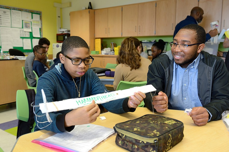A 6th grader  holds his plastic claw design while an older student looks on