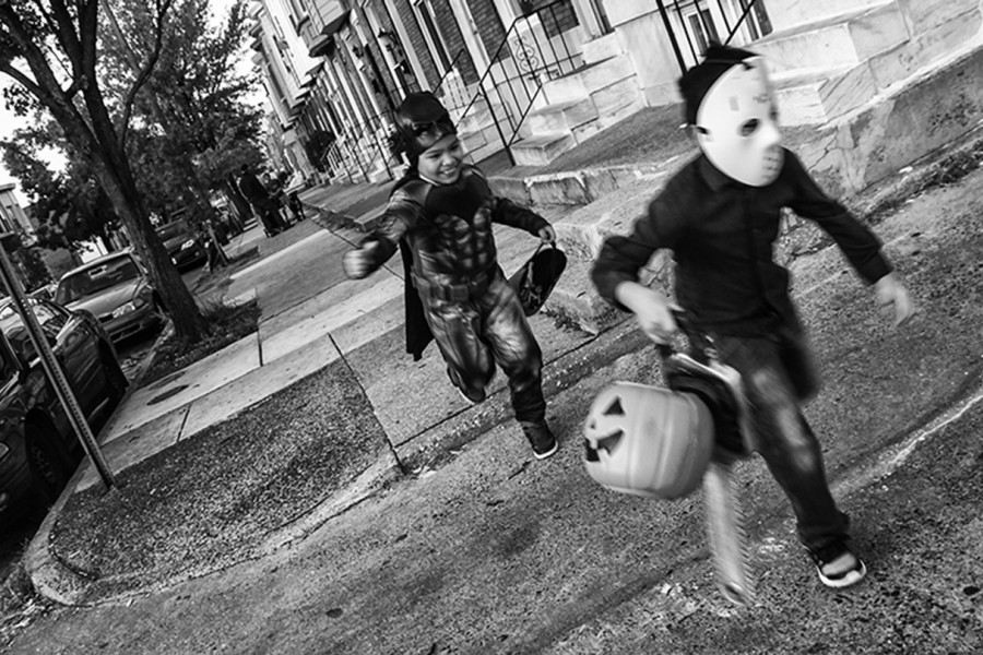 Two boys run in Halloween costumes
