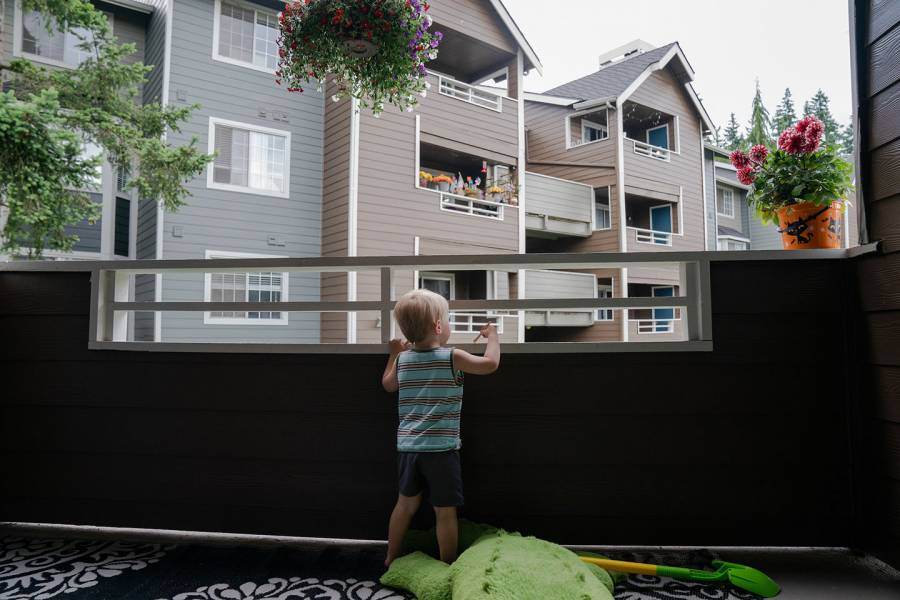 A toddler looks off a balcony at an apartment complex