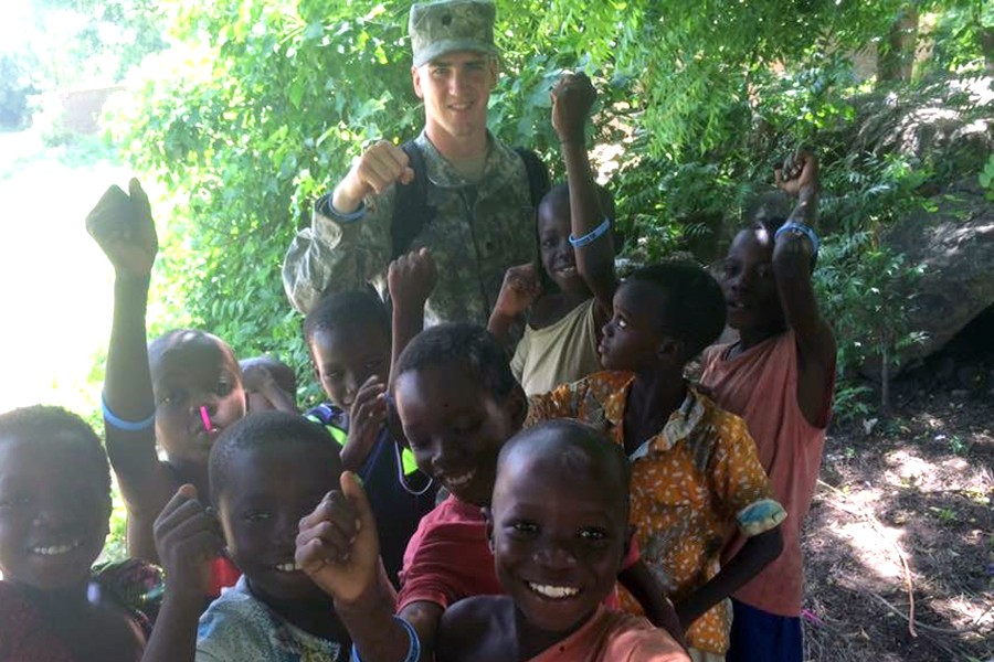 A man in military fatigues with a crowd of children