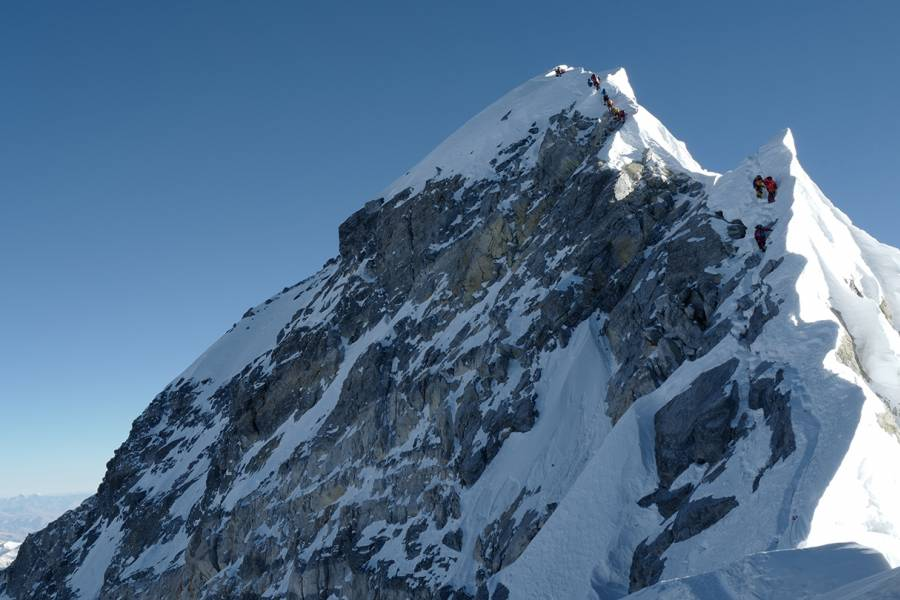 Climbers climb a mountain ridge over Everest