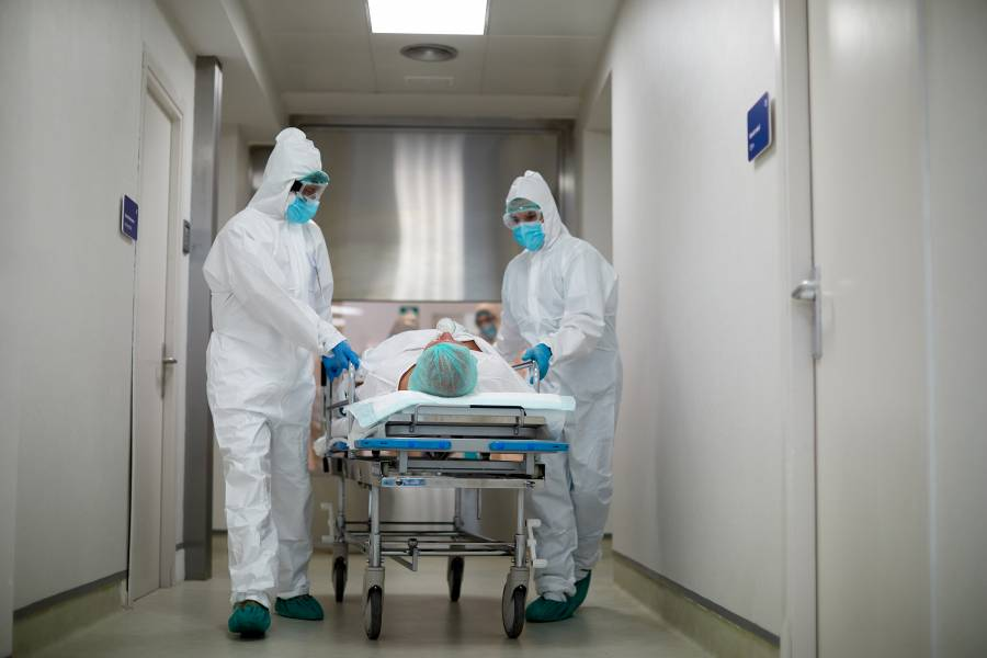 Hospital staff in personal protective equipment and masks transport a patient to the ICU