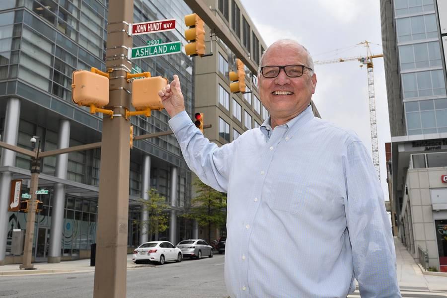 John Hundt posing in front of his new ceremonial street sign