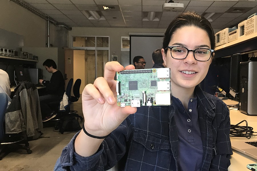 A woman holds up a small green computer chip to the camera