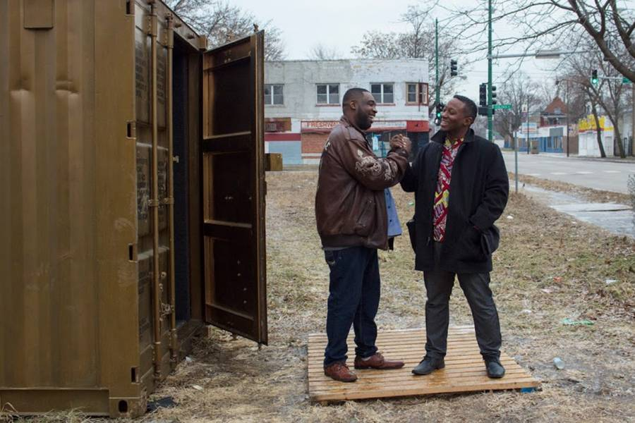 Two men shake hands outside of a gold shipping container in Chicago