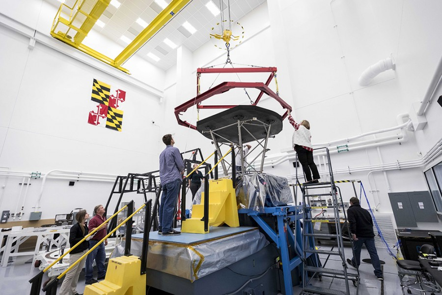 In a giant lab room featuring the Maryland flag on a wall, a team inspects the heat shield and prepares to box it for shipping