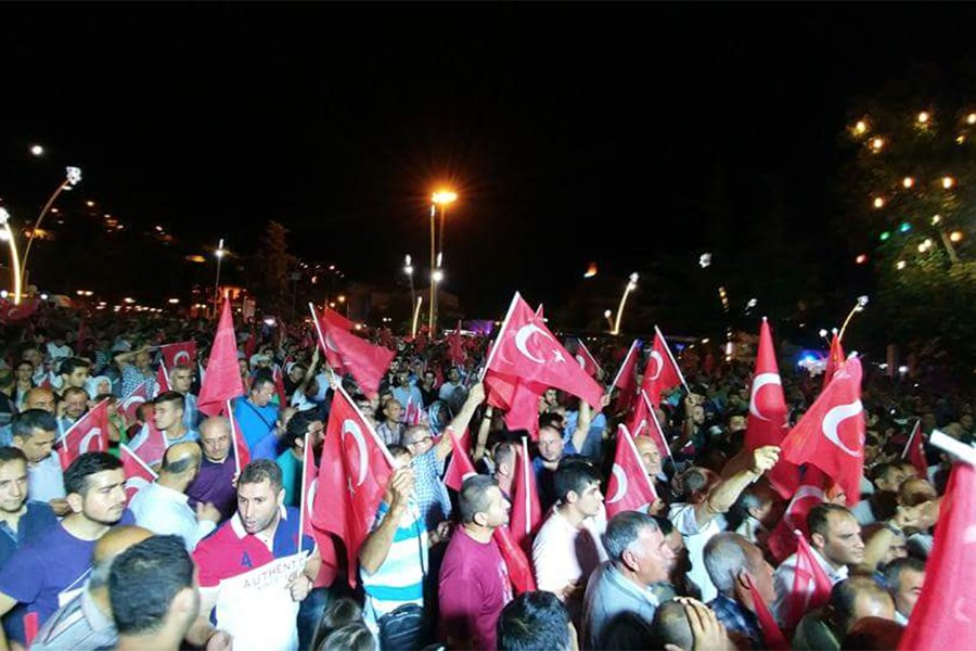 Turkish people wave flags and assemble to protest the military coup