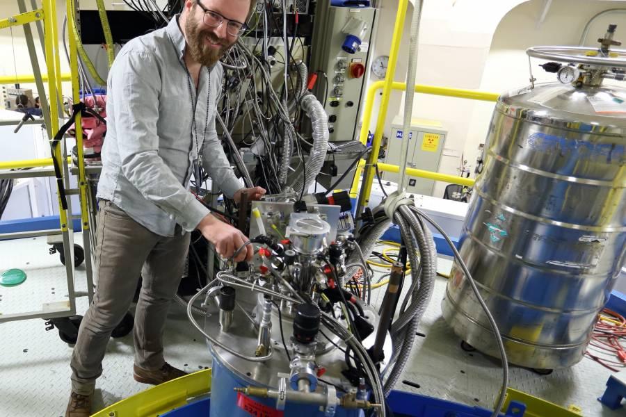 A man adjusts a piece of sensitive lab equipment