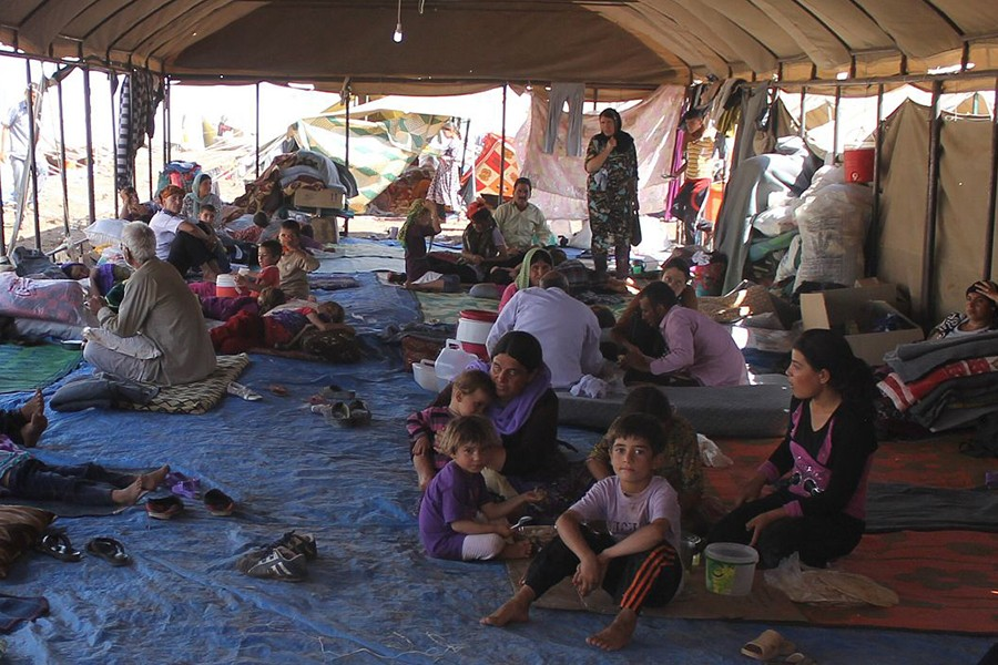 Photo shows people sitting and standing in an open-air tent with makeshift walls from blankets and a dirty tarp floor