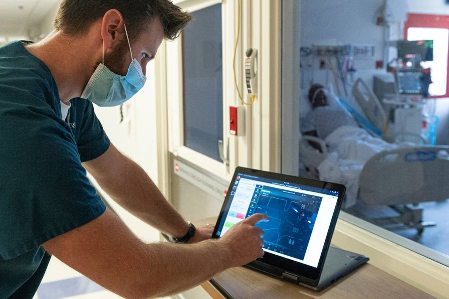 Jonathan Cope, respiratory therapy staff, uses a robotic system to remotely control ventilators