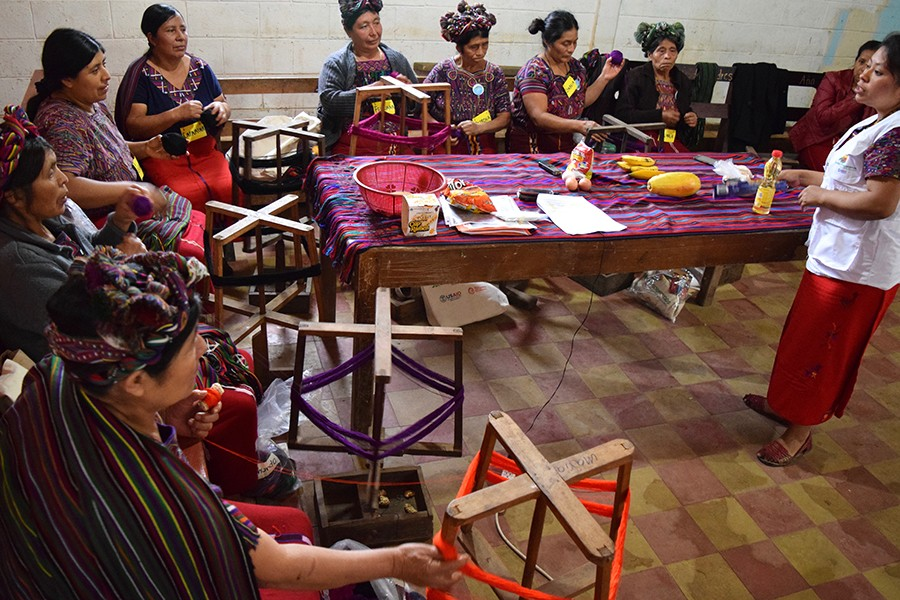 Women wearing traditional headdresses and clothing learn a basketweaving technique