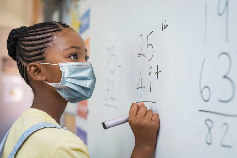 A little girl in a mask practices addition on a school whiteboard