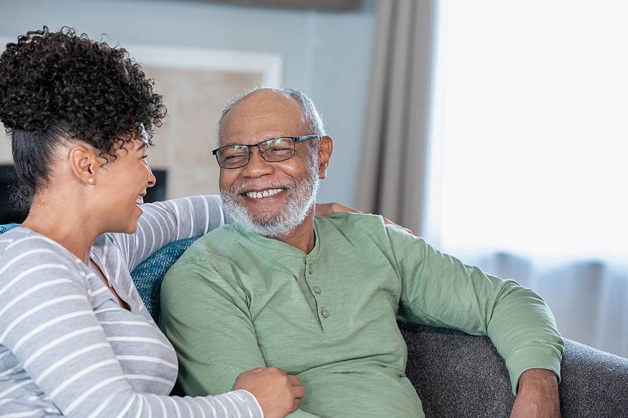 Adult daughter conversing affectionately with smiling father