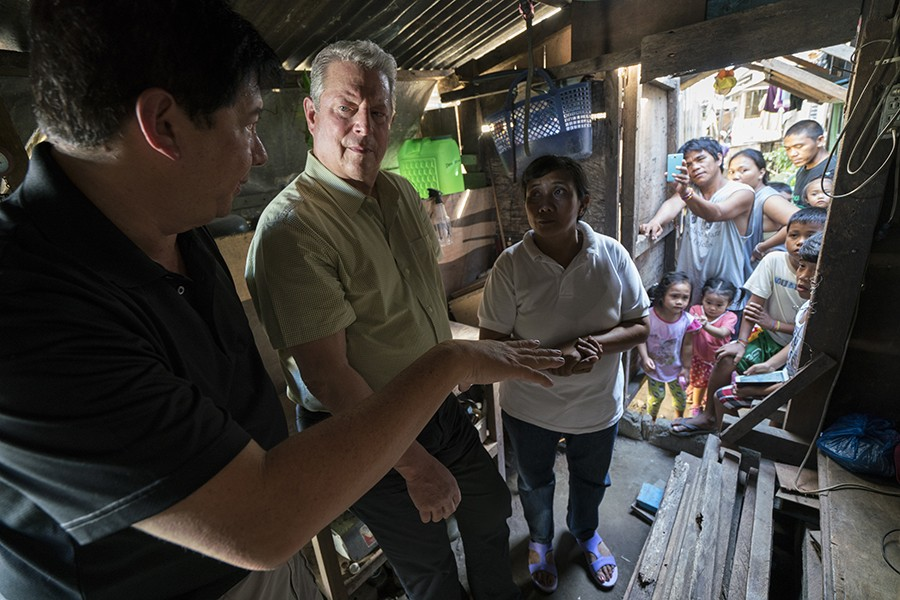 Al Gore stands in a small wooden building and speaks to two people