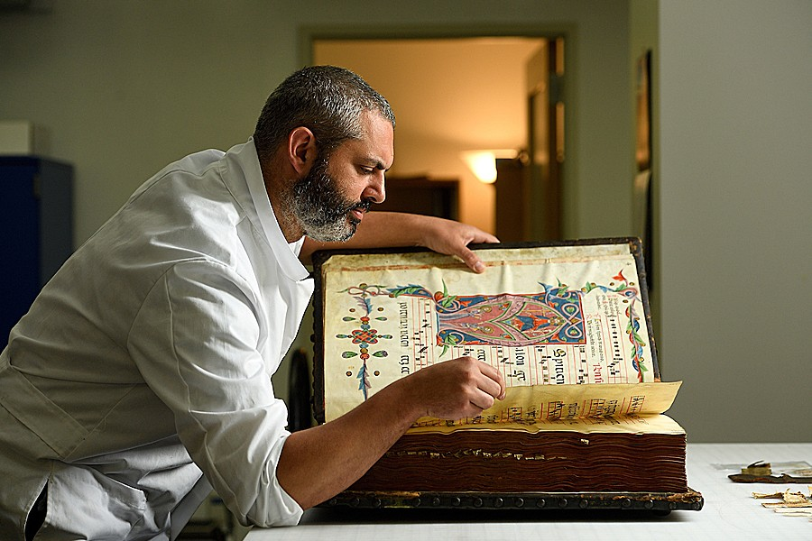 Book conservator Alessandro Scola with the 40-pound medieval manuscript he's currently working on.