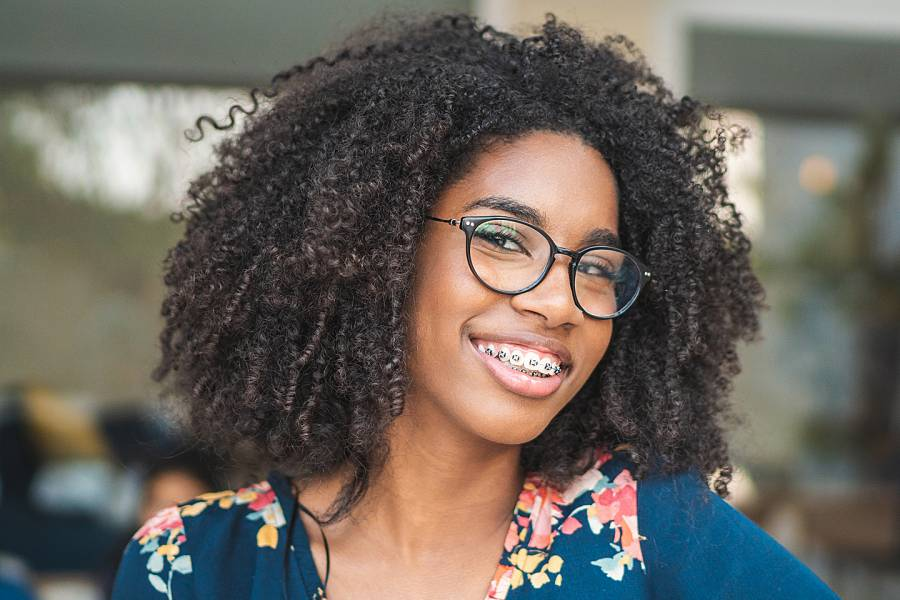 Smiling woman with braces and eyeglasses