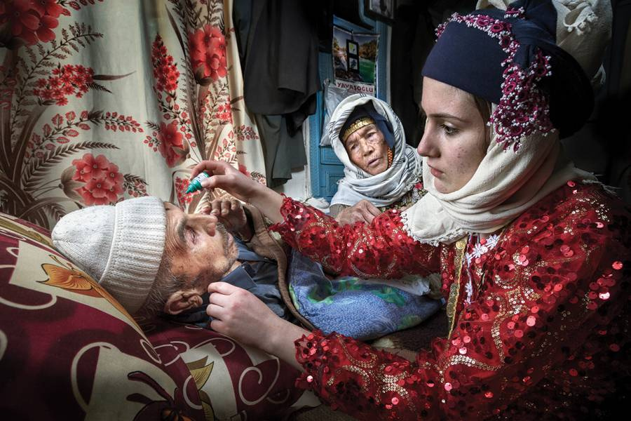 A woman administers eyedrops to her grandfather