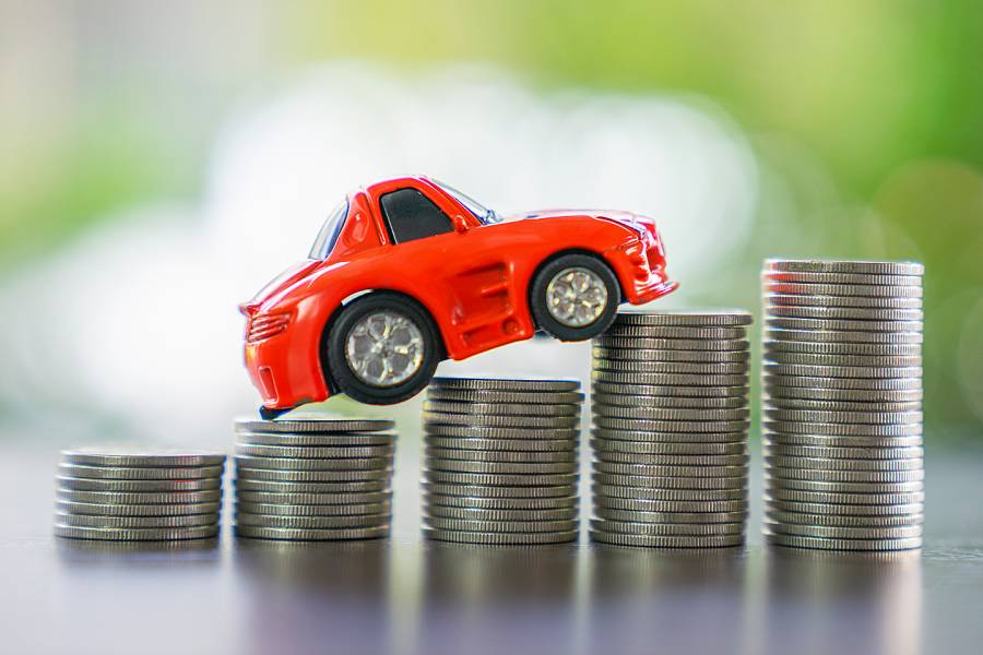 Toy car riding over stacks of coins