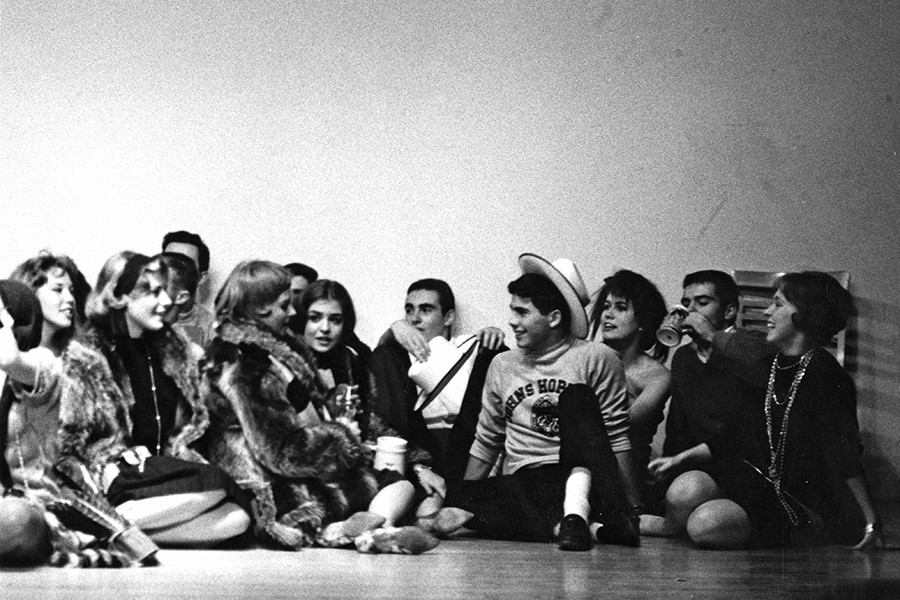 A grainy black and white photo shows male and female students sitting on a floor together