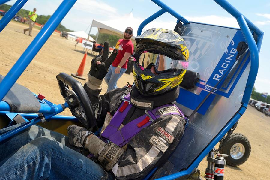 Student in racing gear inside a baja car