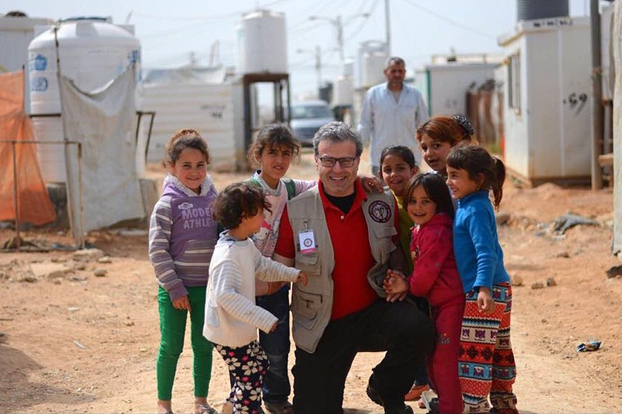 A man kneels beside a group of children in a Syrian refugee settlement