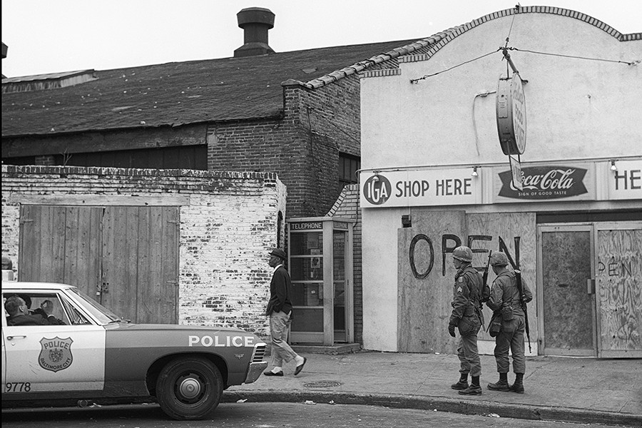 In a black and white photograph, a black man in a suit walks past boarded up shop windows, two armed soldiers, and an idle police cruiser