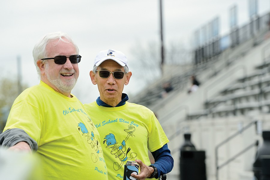 Two men in neon yellow tee shirts stand in the bleachers of Homewood Field