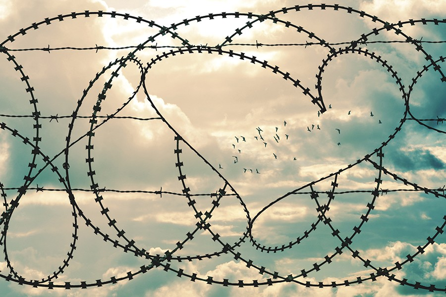 Barbed wire forms a fence, with a heart in the negative space