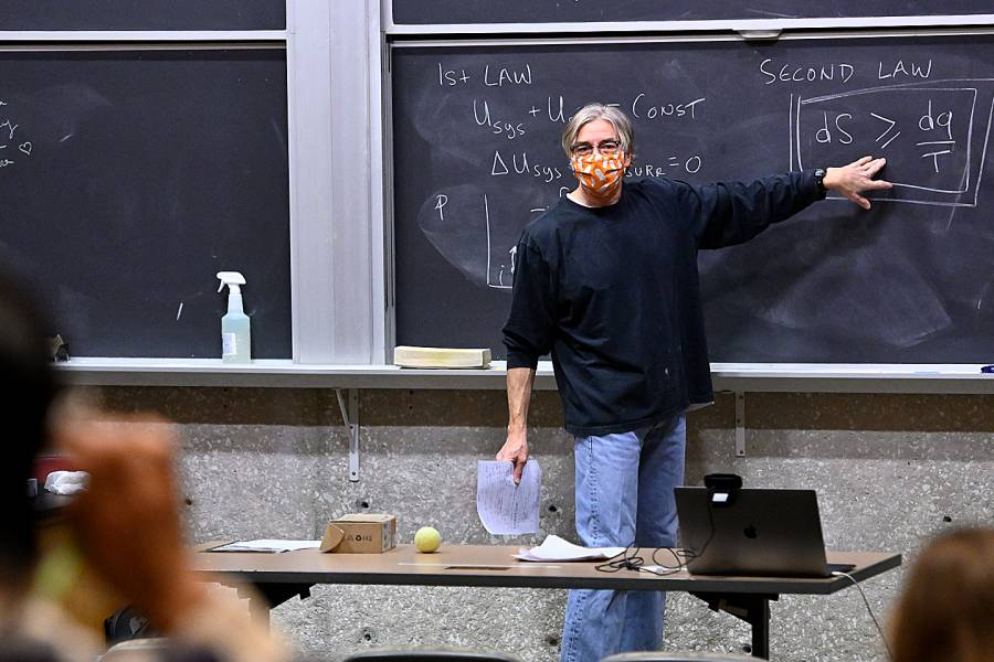 Biophysical Chemistry Professor Doug Barrick, wearing a mask, stands by a blackboard in front of his class
