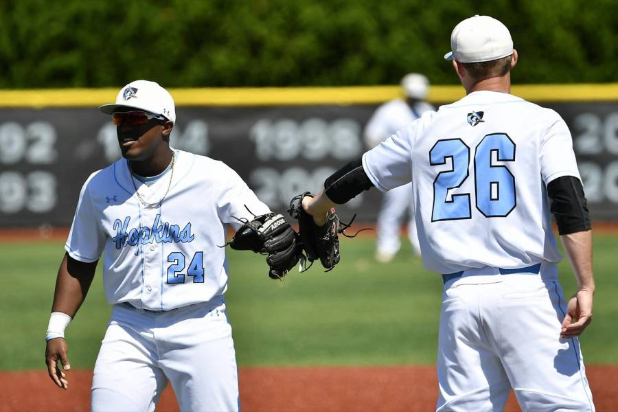 Johns Hopkins baseball players touch gloves