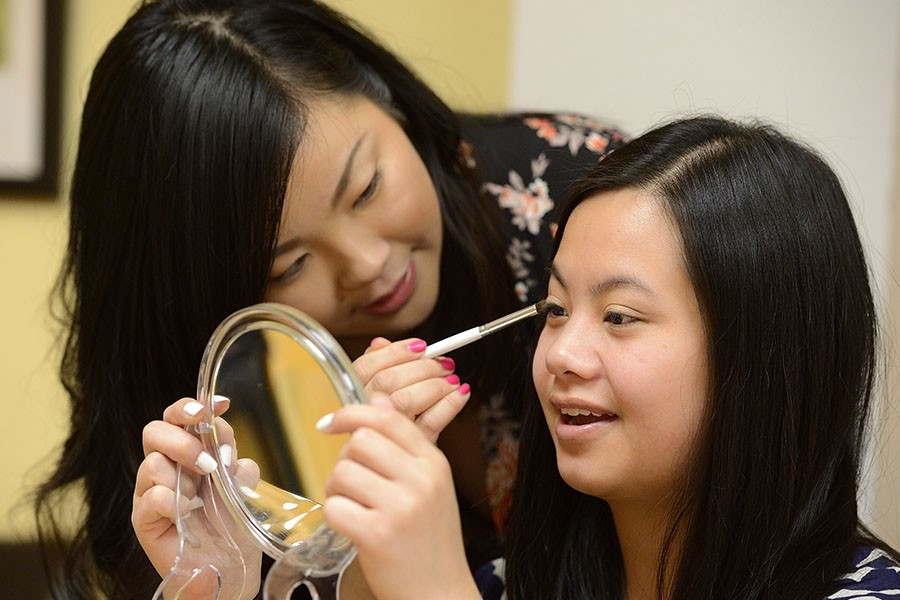 Teacher demonstrates eye shadow application on a student