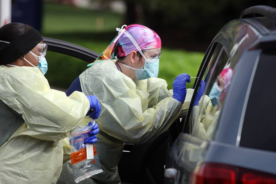 Two health care providers test a driver at a drive-through test site