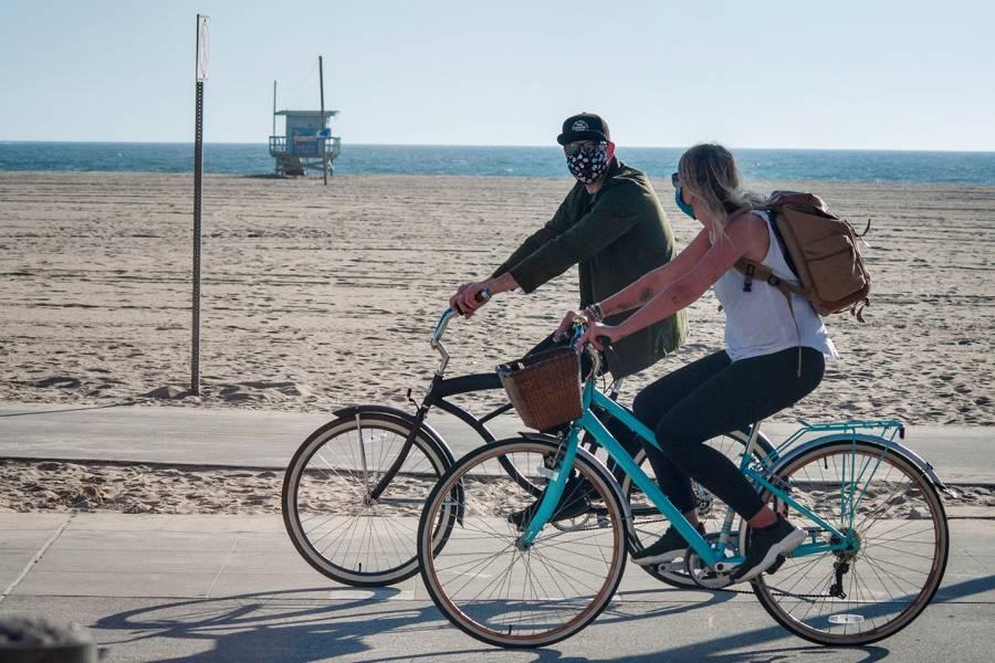 A couple rides bikes near a beach