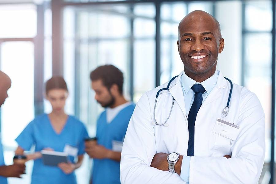 Smiling physician with other medical professionals behind him