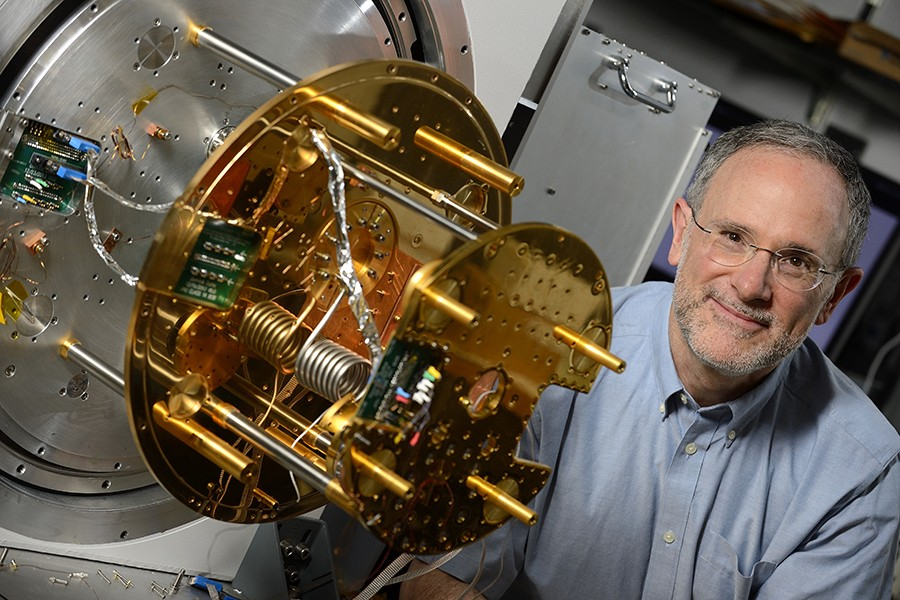 Charles L. Bennett poses with gold and silver WMAP device